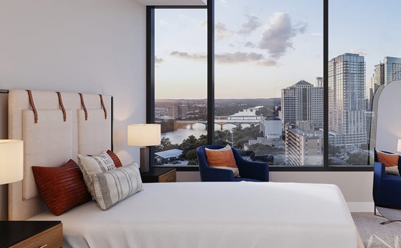 spacious bedroom with city views through a large window